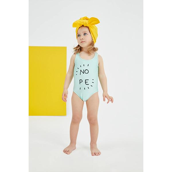 Little girl with green swimsuit with 'Nope' slogan black glitter print detail in front of the wall