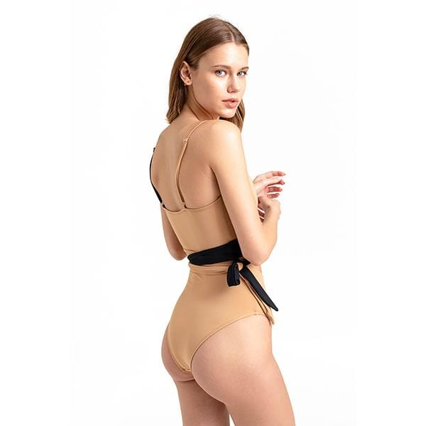 A model woman wears movom branded black and tan colours  valencia wrap swimsuit