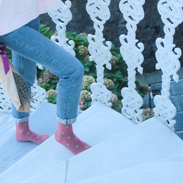A girl with Fundaze branded pink bamboo socks with Italian Greyhound pattern