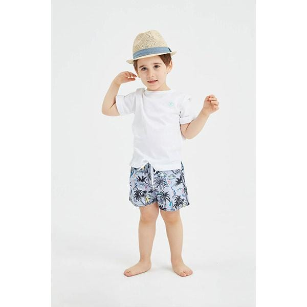 Little boy with sailboat patterned swim shorts