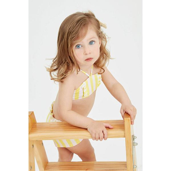 blue-eyed little girl on a ladder with yellow and white striped lilou bikini
