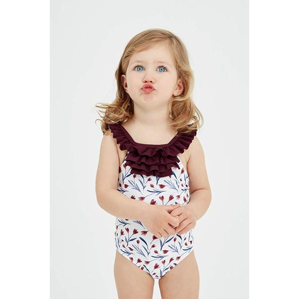 Blue-eyed little girl wears frill detail floral patterned burgundy swimsuit