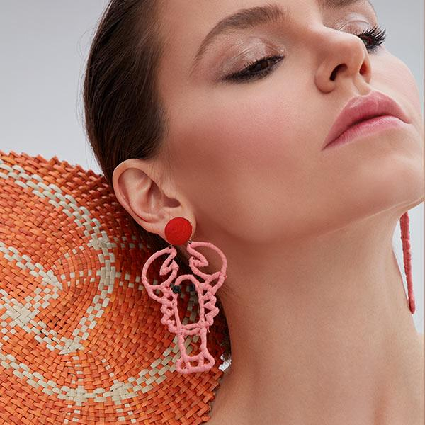 woman wears silk thread and raffia hand-knitted lobster in form earrings