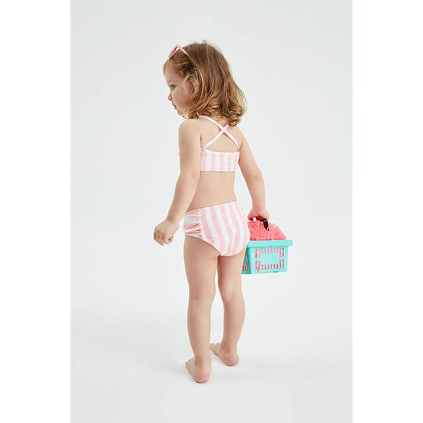 blue-eyed little girl on a ladder  with pink and white striped bikini set