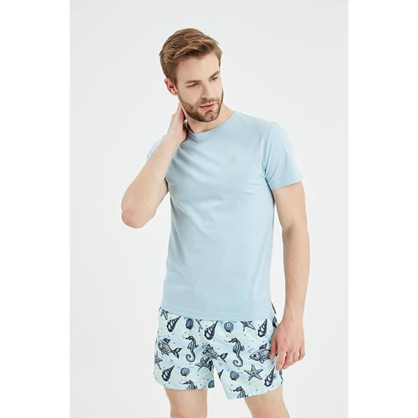 A man with underwater patterned men swim shorts and blue t-shirt
