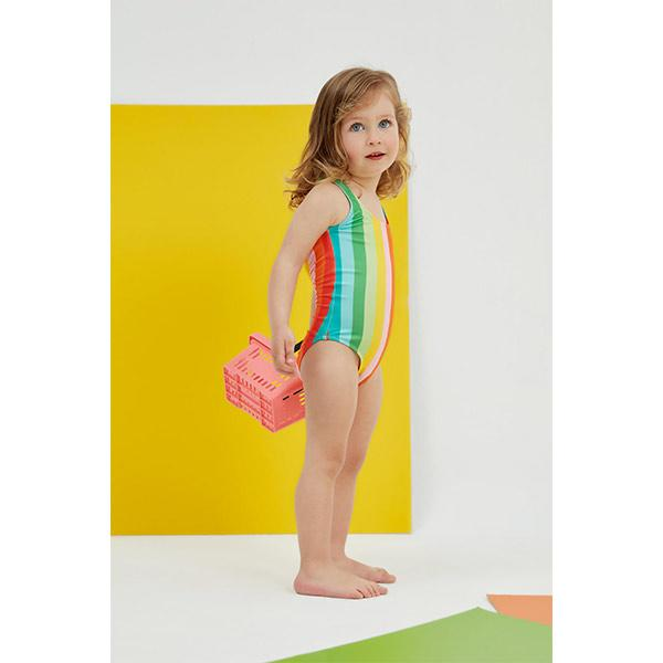 blue-eyed little girl wears peralina striped swimsuit with a rainbow pattern