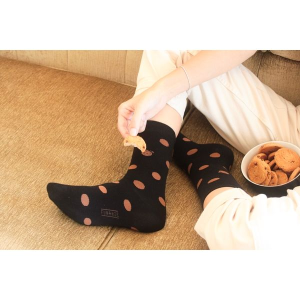A man Fundaze branded black with bamboo socks with polka dot cookie pattern
