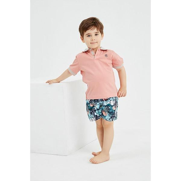 Little boy patterned green swim shorts and pink t-shirt