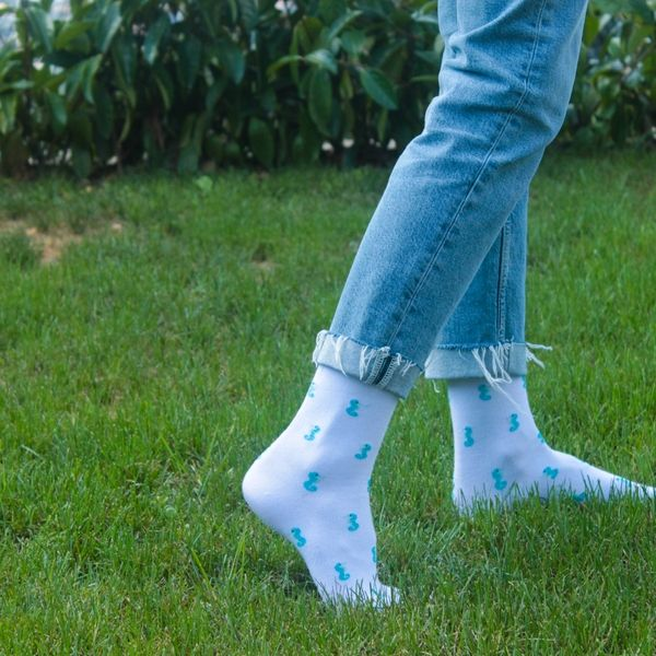 A girl with Fundaze branded white bamboo socks with Seahorse pattern