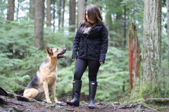 Dog owner who has done dog training classes Vancouver on a rain forest hike with her dog. Her German shepherd gazes at her lovingly.
