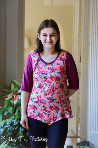 Woman modeling Hope top length with one placket on the top, v hem and pink floral fabric.