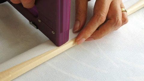 Stapling the canvas onto the stretchers