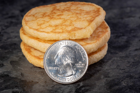 Stacked French blinis with quarter dollar coin for size comparison