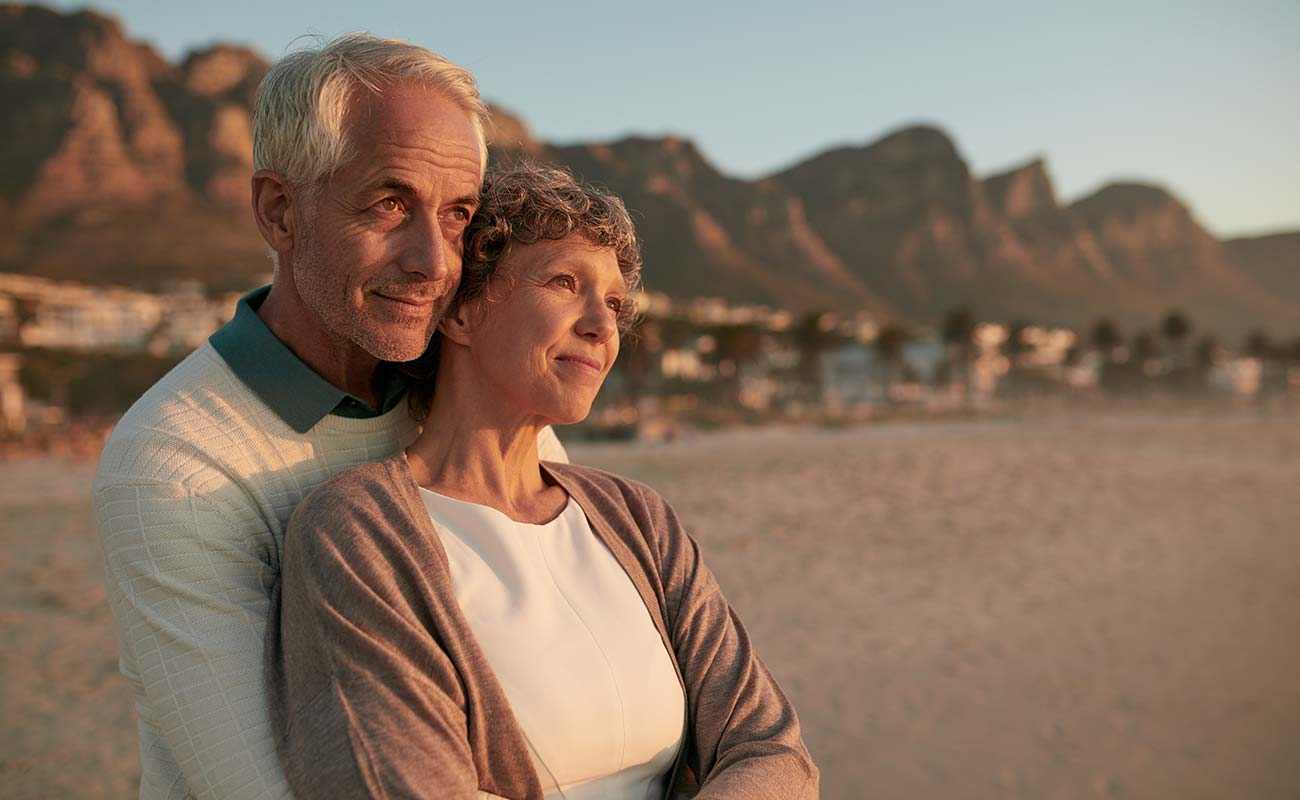 Handsome senior couple snuggling and looking out at the beach
