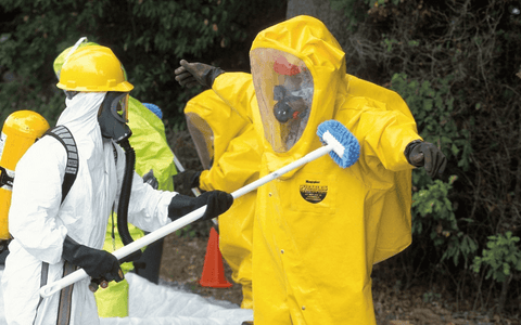 two men in chemical protective clothing