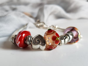 Pandora style bracelet with handmade beads in red color.