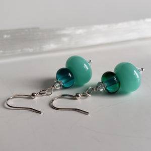 Luxurious festive earrings in teal color