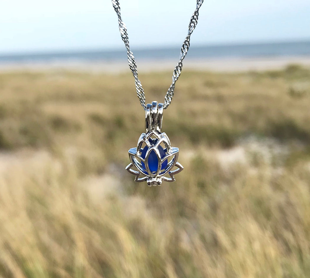 lotus locket necklace with cobalt blue sea glass take at the beach