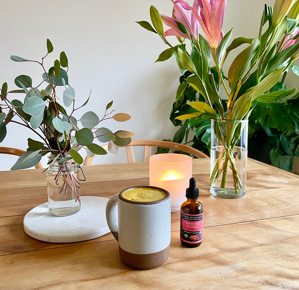 DIY golden milk with immune tonic and candle on table with flowers