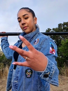 San Francisco Native throwing up West side with her hands wearing the Melting Pot jean jacket.