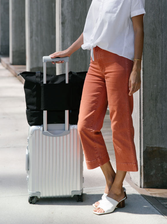 woman standing next to luggage with Catalina on handle