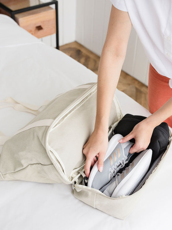 woman packing shoes into bottom pocket