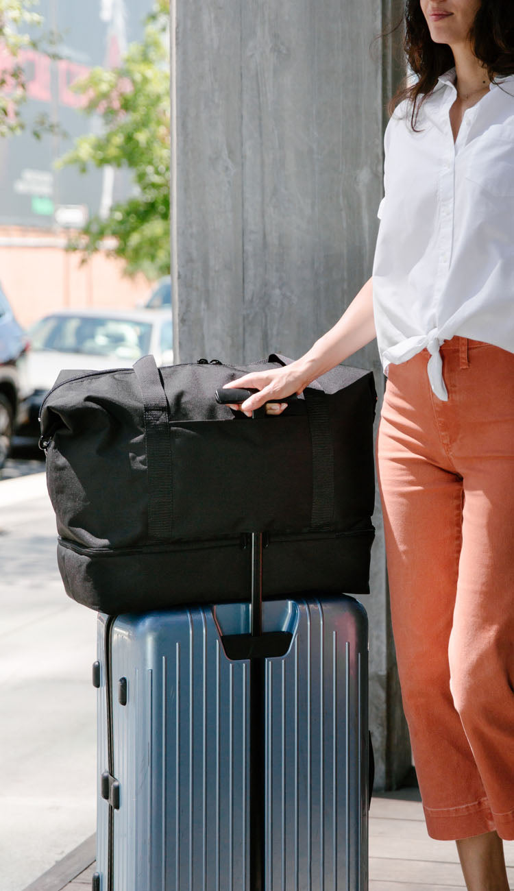 woman next to Catalina Deluxe attached to luggage handle