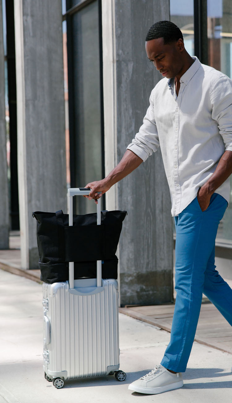 man with Catalina Deluxe Tote on luggage