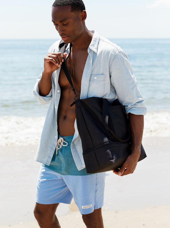 man at beach with The Catalina Deluxe Tote on shoulder