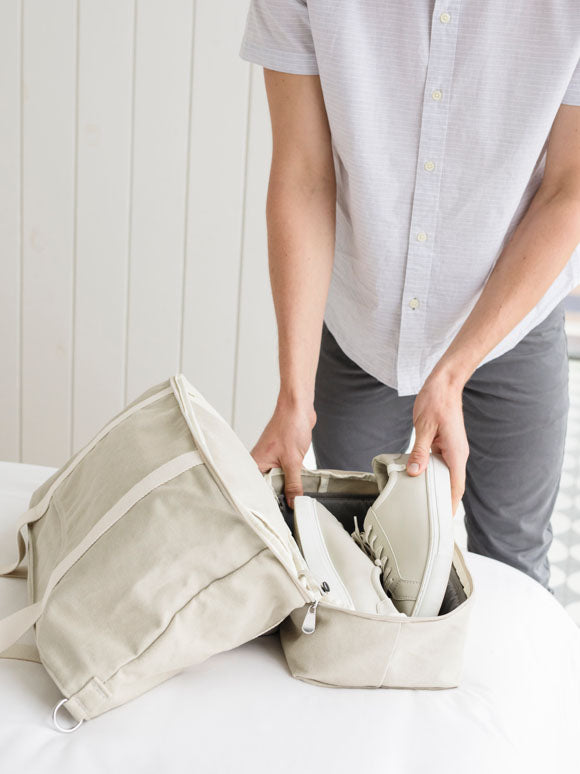 man packing shoes into bottom pocket