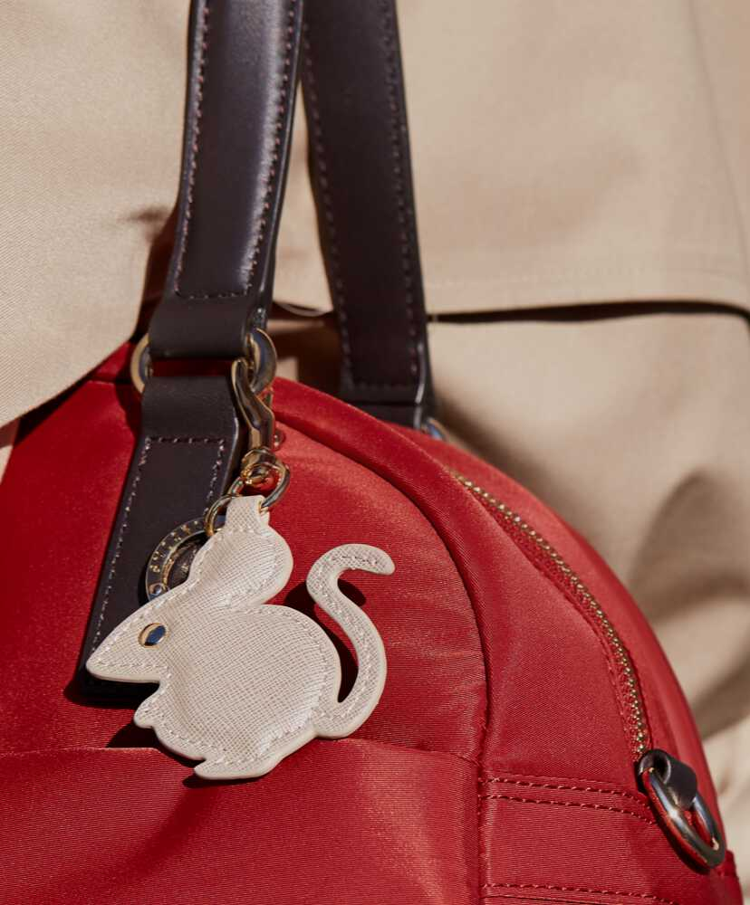 woman with rat charm on red bag