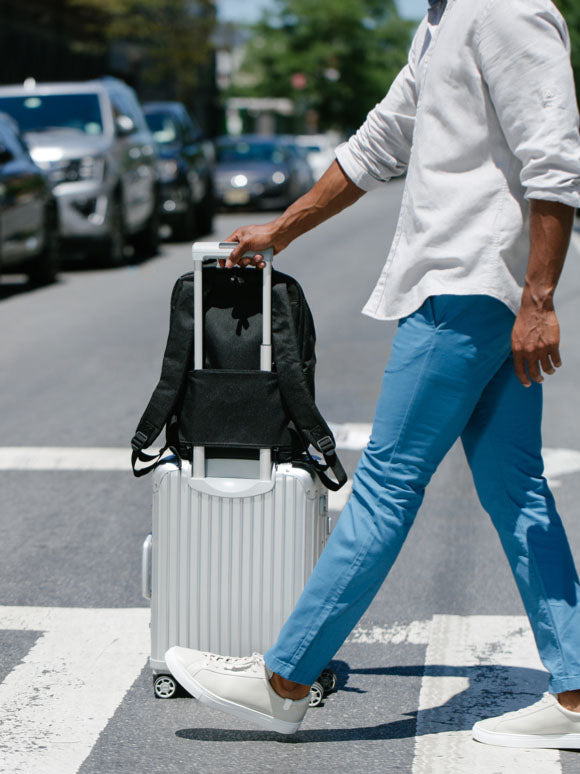 man walking across cross-walk with luggage
