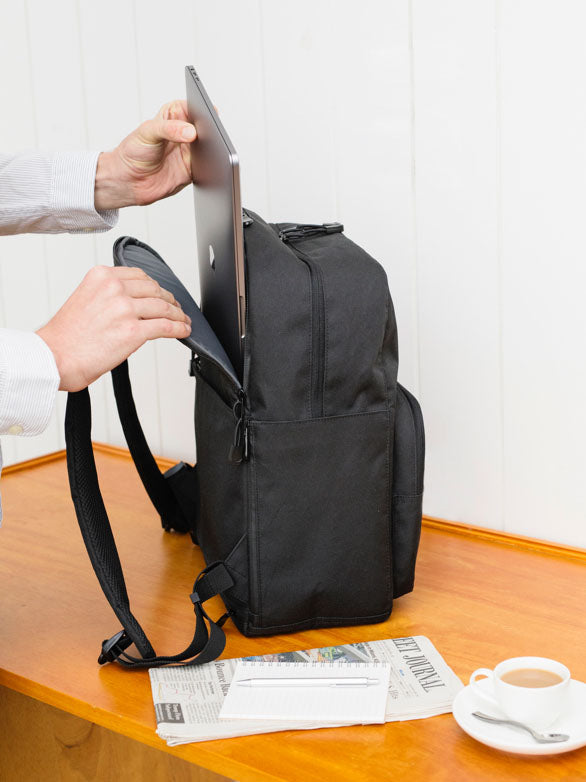 man putting laptop in backpack