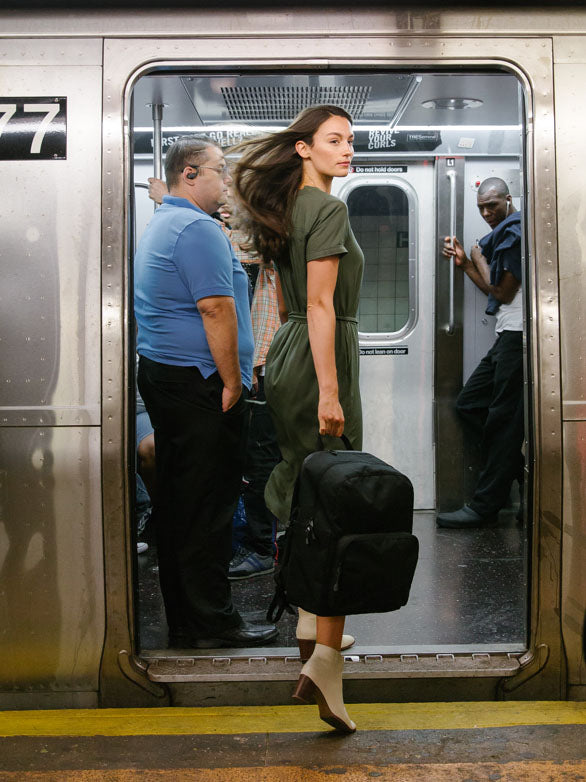 woman entering subway train with backpack