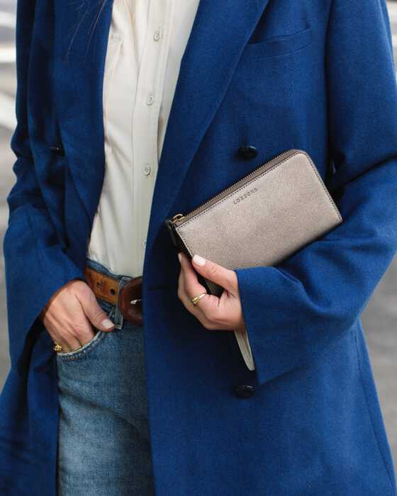 woman in blue coat holding Leather Wallet in graphite