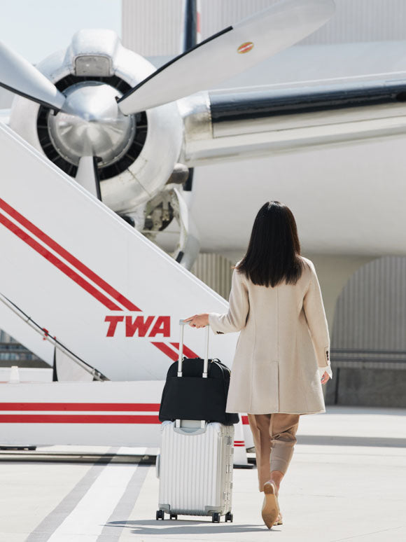 woman walking toward plane with bag on luggage