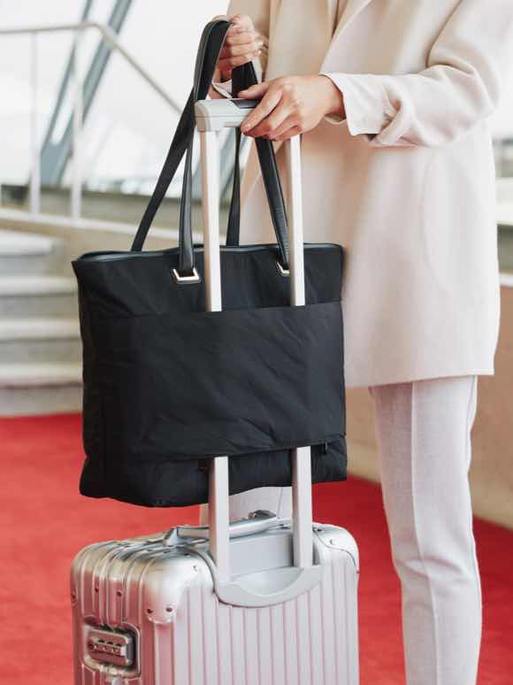 woman lifting Seville Tote off luggage