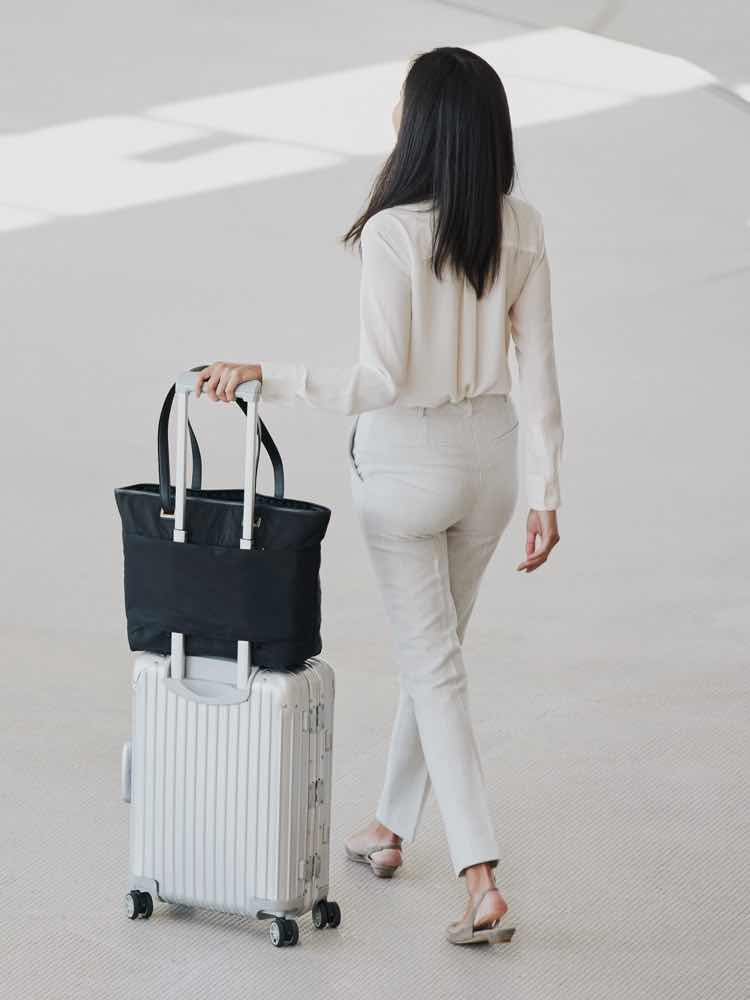 woman walking with Seville Prima secured to luggage