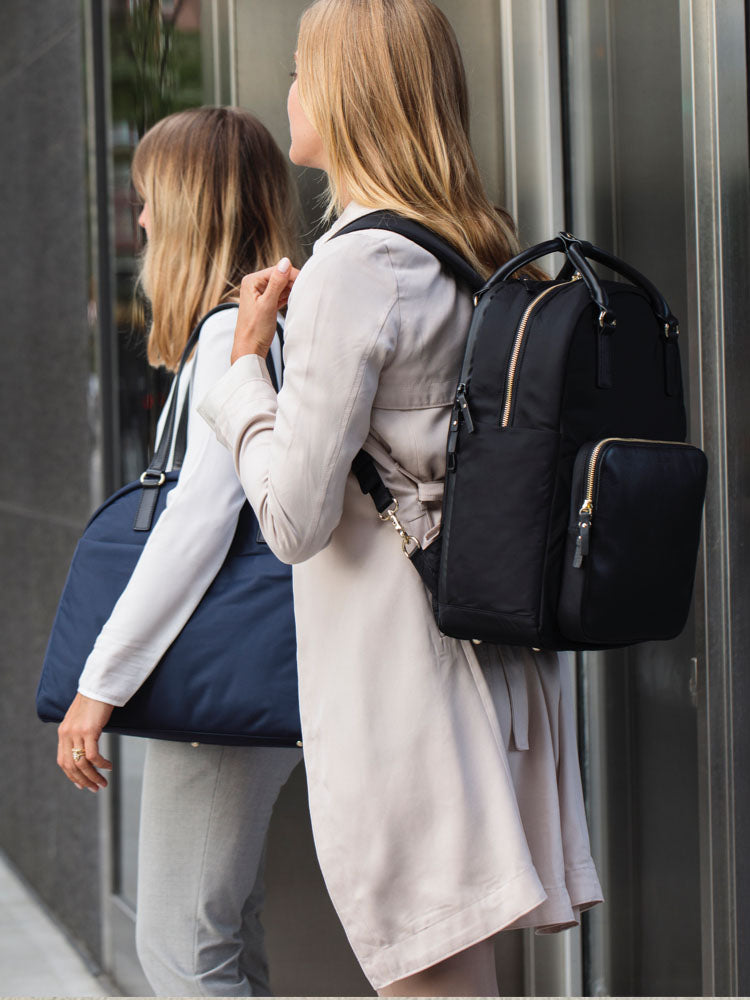 two women carrying bags on shoulders