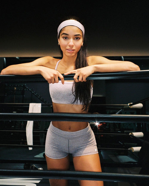 @yoventura wearing an alo yoga headband, sports bra, and shorts during a boxing class.