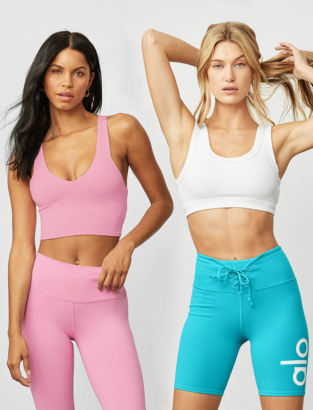One woman wearing a light pink workout set with a sports bra tank top and high-waisted leggings standing alongside another woman wearing bright blue high-waisted biker leggings with a drawstring and a white sports bra.