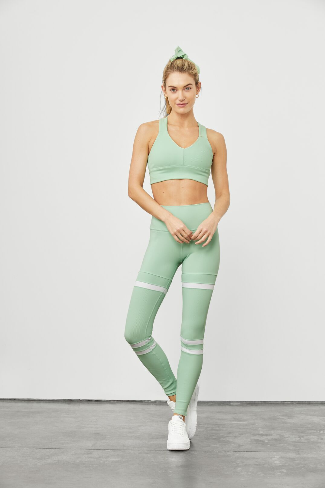 A woman posing against a white wall wearing sporty leggings and sports bra tank.