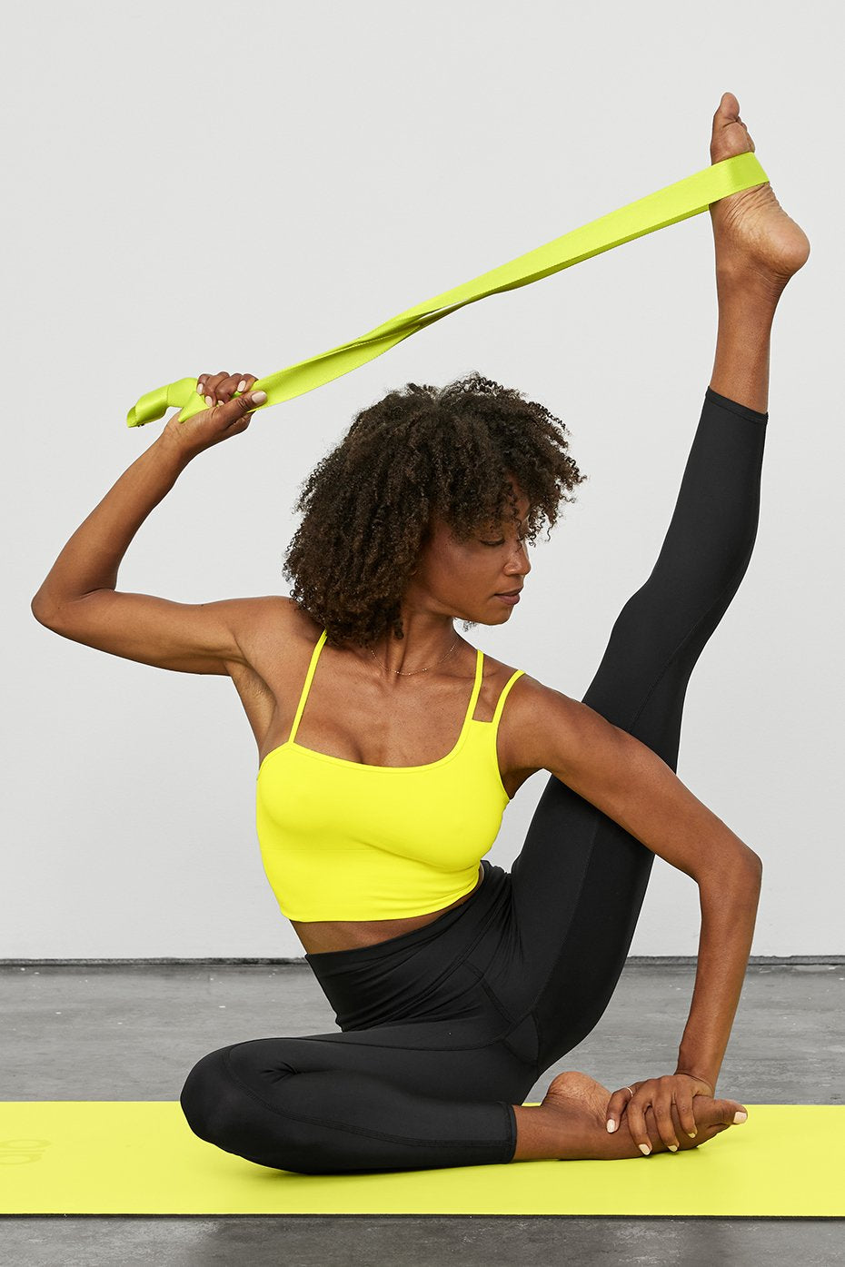 Woman using a highlighter yellow yoga strap to deepen her practice on the mat.