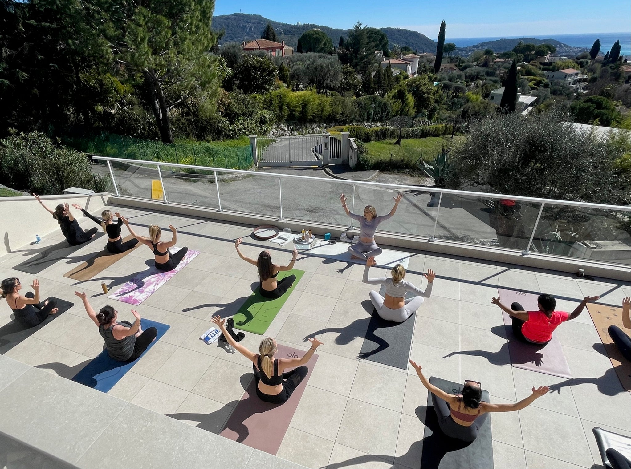 Group of people safely gathering for outdoor yoga class in Nice, France per COVID-19 safety regulations and guidelines.