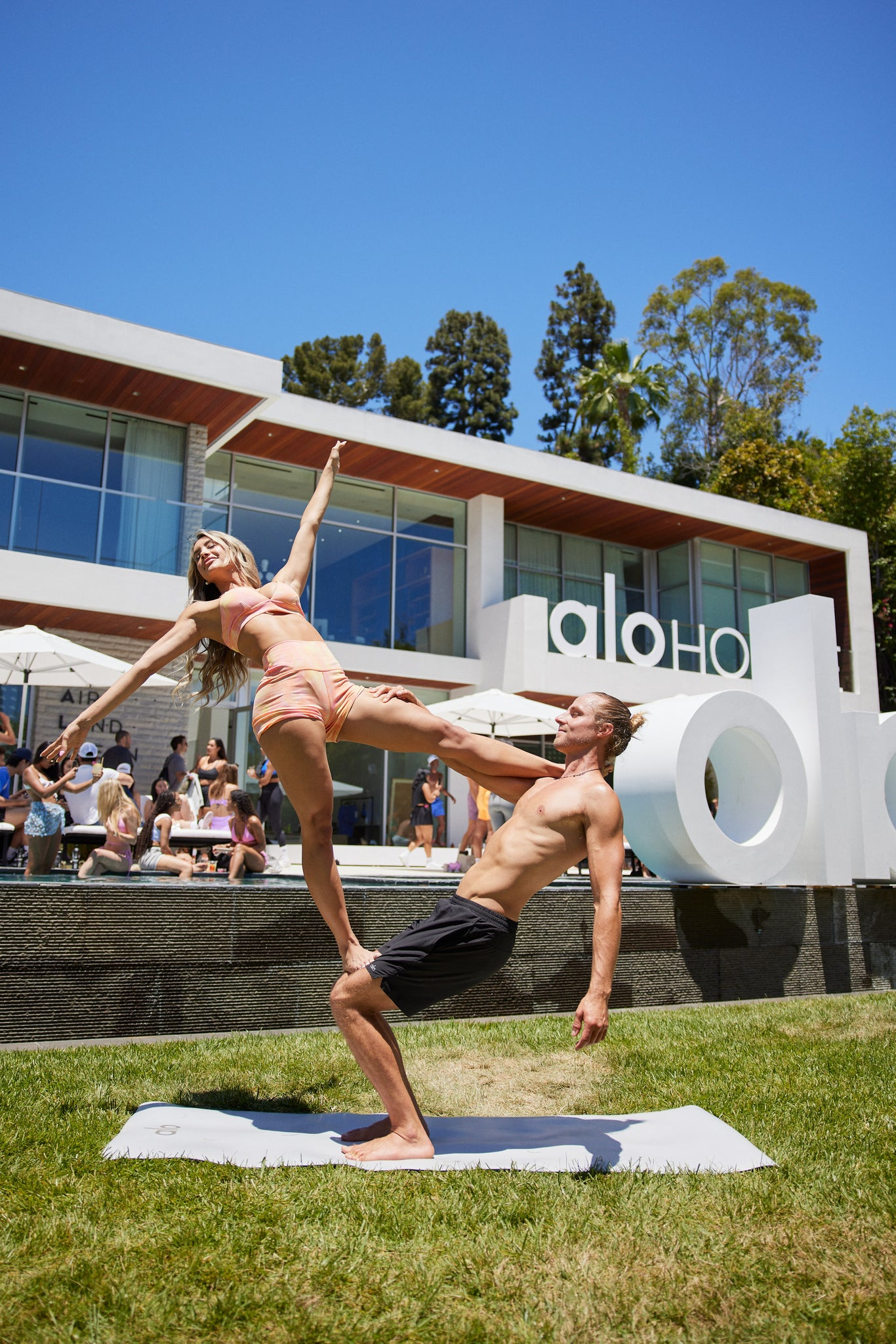 A man and woman practicing acro yoga on the lawn at Alo House.