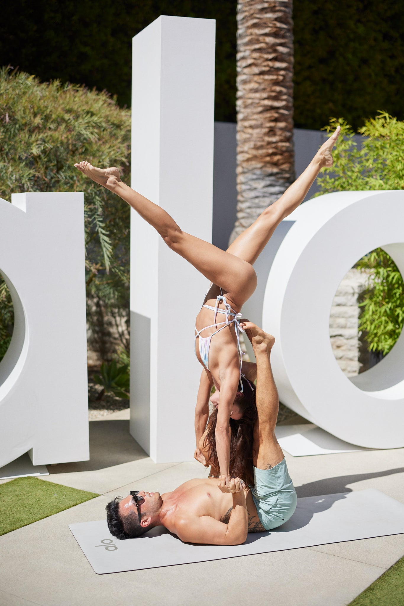 A man and a woman performing acro yoga in front of the large Alo block letters at Alo House.