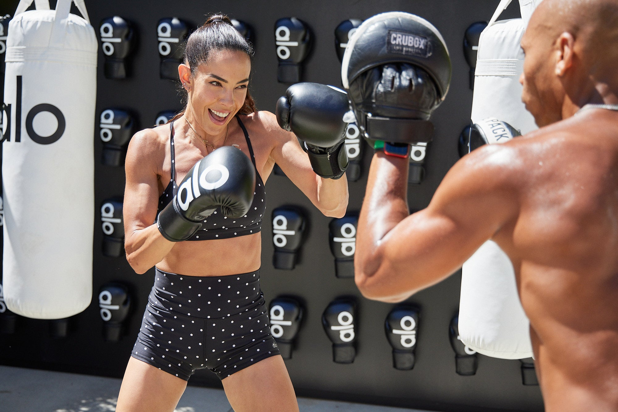 @Kupahjames leading a woman wearing the Airlift Intrigue Polka Bra and High-Waist Short Set through a boxing session.