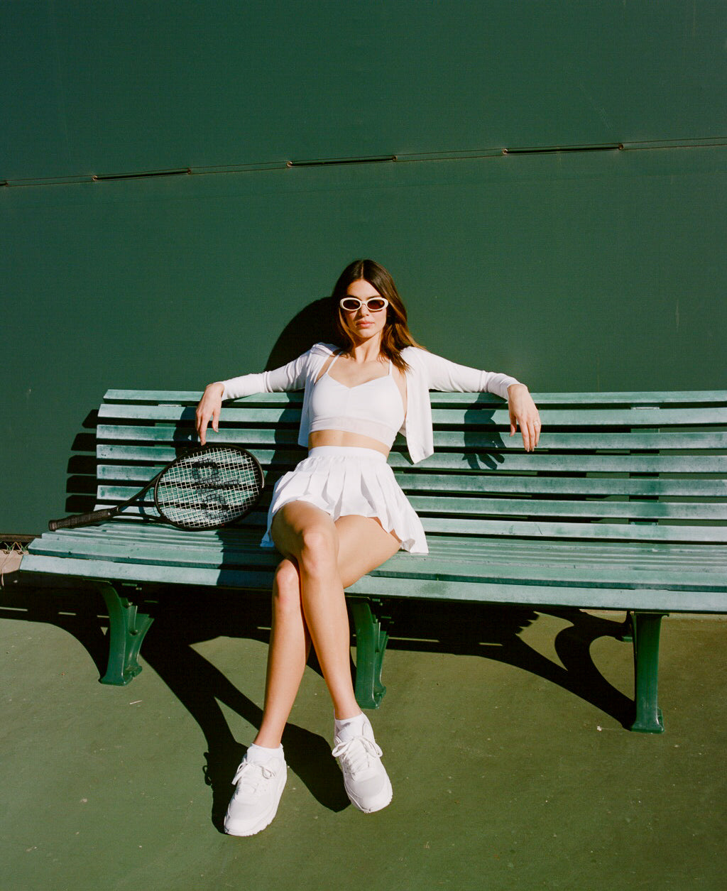 @kendalljenner wearing an all-white tennis skirt outfit with trendy white sunglasses while sitting on the sidelines of a tennis court.