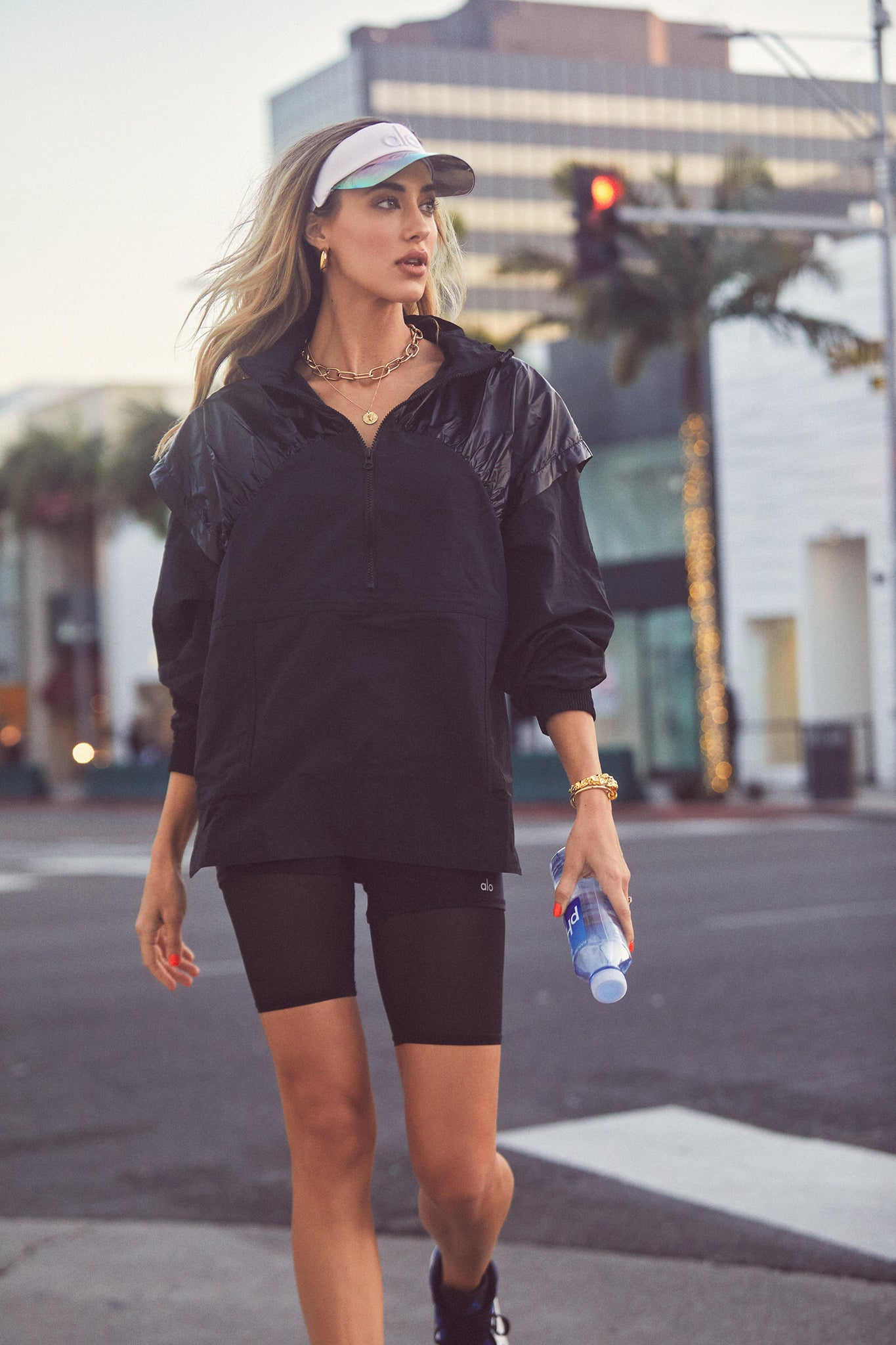 @jessicamichel wearing black biker shorts, an oversized quarter zip jacket, and a holographic visor.
