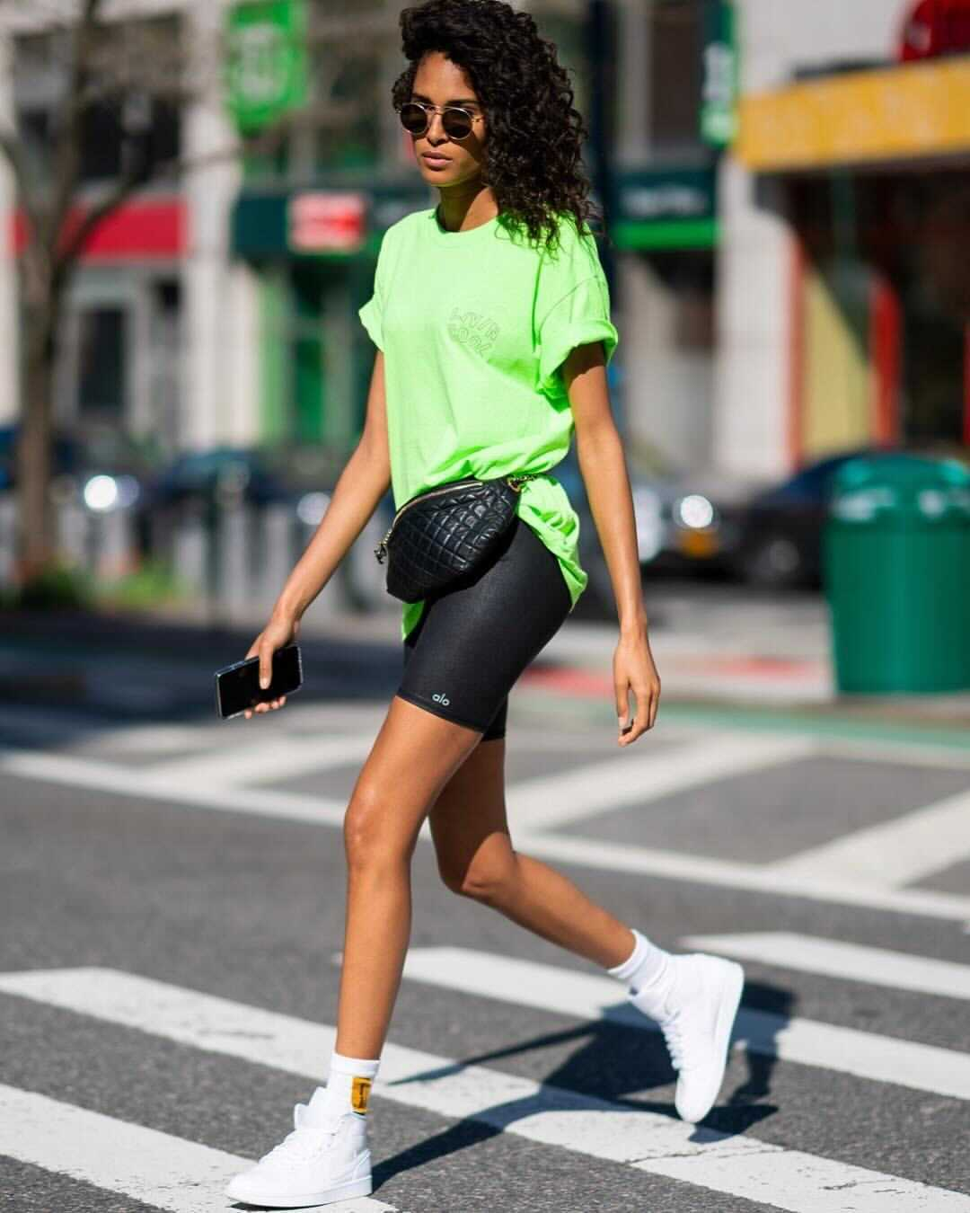 @cindybruna wearing an oversized neon green t-shirt with black biker shorts and a fanny pack while walking around the streets of New York.